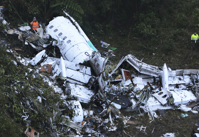 Rescue workers stand at the wreckage site of a chartered airplane that crashed in a mountainous area outside Medellin, Colombia, Tuesday, Nov. 29, 2016. The plane was carrying the Brazilian first  ...