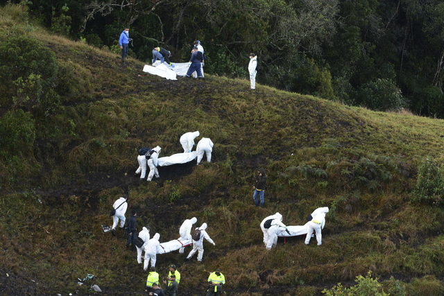 Rescue workers carry the bodies of victims of an airplane crash in a mountainous area near La Union, Colombia, Tuesday, Nov. 29, 2016. The plane was carrying the Brazilian first division soccer cl ...