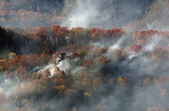 Smoke surrounds a home as seen from aboard a National Guard helicopter near Gatlinburg, Tenn., Tuesday, Nov. 29, 2016. Thousands of people have fled deadly wildfires that have destroyed hundreds o ...