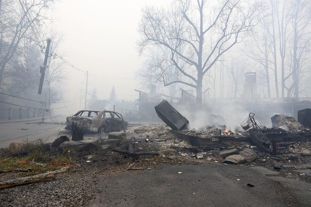 A structure and vehicle are damaged from the wildfires around Gatlinburg, Tenn., on  Tuesday, Nov. 29, 2016.  Rain had begun to fall in some areas.. (Michael Patrick/Knoxville News Sentinel via AP)