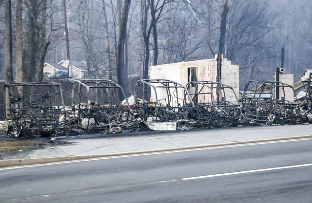 Burned out frames side-by-side utility vehicles sit at the side of the road in Gatlinburg, Tenn., Tuesday, Nov. 29, 2016. The fatal wildfires swept over the tourist town the night before, causing  ...