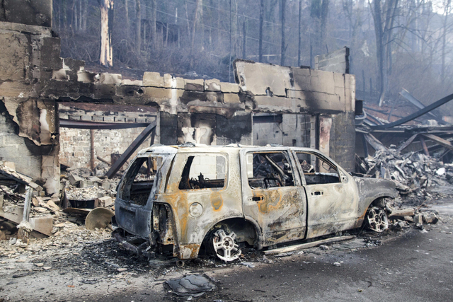 A scorched vehicle sits next to a burned out building in Gatlinburg, Tenn., on Tuesday, Nov. 29, 2016. The fatal fires swept over the tourist town the night before, causing widespread damage. (Eri ...