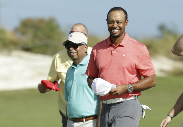 Tiger Woods, right, walks off the 18th green with Pawan Munjal, CEO of Hero MotoCorp, left, during the Pro-Am at the Hero World Challenge golf tournament, Wednesday, Nov. 30, 2016, in Nassau, Baha ...