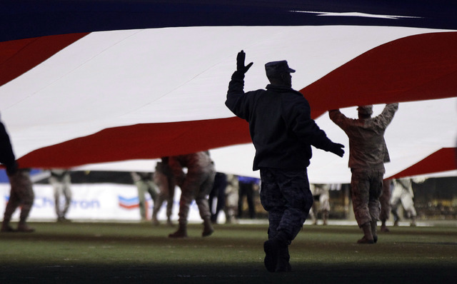 Military personnel from Nellis Air Force Base spread a giant American flag over the field before the start of the Maaco Bowl NCAA college football game between Arizona State and Boise State, Thurs ...