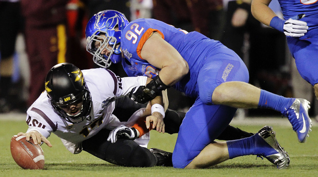 In this Dec. 22, 2011, file photo, Arizona State quarterback Brock Osweiler (17) reaches for the ball after a bad snap as Boise State defensive end Shea McClellin (92) defends in the first half of ...