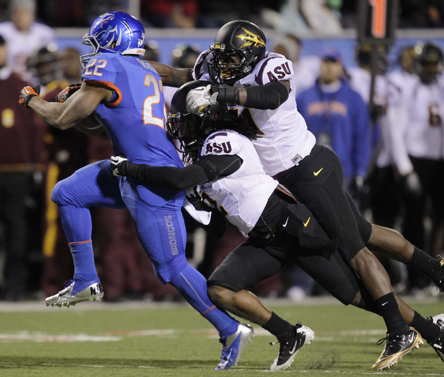 Boise State running back Doug Martin (22) surges forward against Arizona State safety Eddie Elder (2) and linebacker Anthony Jones (31) during the second quarter of the Maaco Bowl NCAA college foo ...