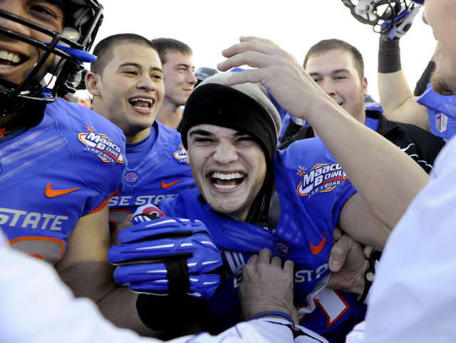 Boise State kicker Michael Frisina, center, is surrounded by teammates as he celebrates after they defeated Washington at the MAACO Bowl NCAA college football game on Saturday, Dec. 22, 2012, in L ...
