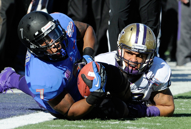 Boise State running back D. J. Harper hangs onto the ball after making a sideline reception with Washington's John Glenn defending during first half of the MAACO Bowl NCAA college football game on ...