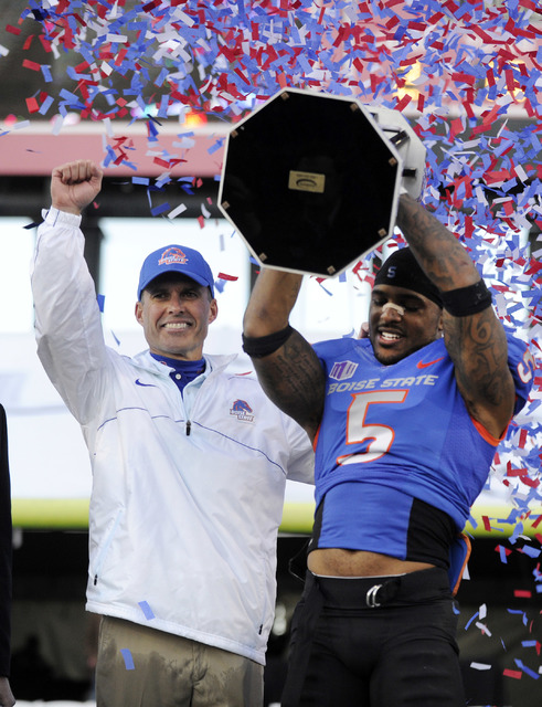 In this Dec. 22, 2012 file photo, Boise State coach Chris Petersen, left, gestures as cornerback Jamar Taylor holds the championship trophy after the MAACO Bowl NCAA college football game against  ...