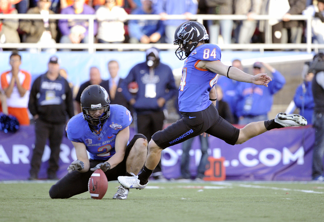 Boise State Matt Miller (2) holds the ball for kicker Michael Frisina (84) who boots the ball during the final minutes of the MAACO Bowl NCAA college football game on Saturday, Dec. 22, 2012, in L ...