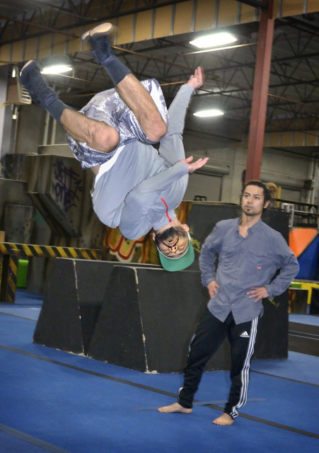 Abenamar Honrubia, aka BenStacks, left, warms up before rehearsing for the Red Bull BC One world championship as Rock Gallego looks on at the Hardcore Parkour studio in North Las Vegas on Tuesday, ...