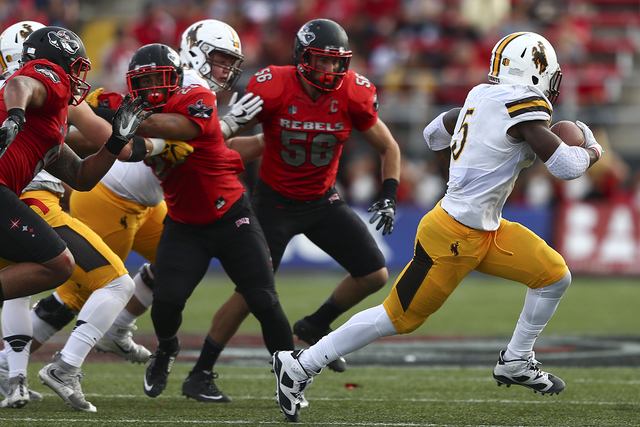 Wyoming running back Brian Hill (5) gets past UNLV defense during a football game at Sam Boyd Stadium in Las Vegas on Saturday, Nov. 12, 2016. UNLV defeated Wyoming 69-66 in triple overtime. (Chas ...