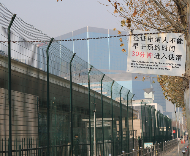 Each weekday morning, a visa line at the US Embassy in Beijing filled with mostly Chinese people spans about three blocks. A sign dangles from a wire Wednesday, Nov. 30, 2016, instructing embassy- ...