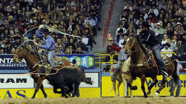 Jade Corkill from Fallon, Nev., left,and partner Clay Tryan from Billings, Mont., rope a calf to a time of 6.0 seconds during the tenth go-round of the National Finals Rodeo at the Thomas & Ma ...
