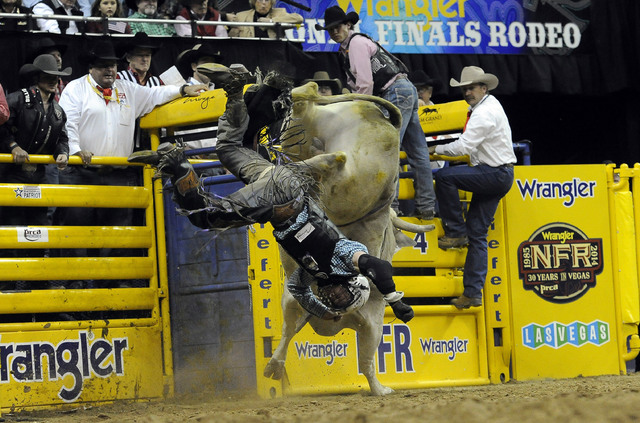 Bull rider Trey Benton III from Rock Island, Texas, is bucked off of Mr. Bull during the tenth go-round of the National Finals Rodeo at the Thomas & Mack Center in Las Vegas, Saturday, Dec. 13 ...