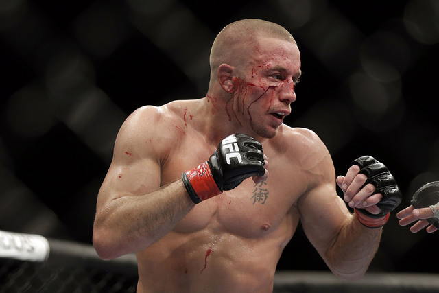 Georges St. Pierre, of Canada, fights Johny Hendricks during a UFC 167 mixed martial arts championship welterweight bout on Saturday, Nov. 16, 2013, in Las Vegas. St. Pierre won by split decision. ...