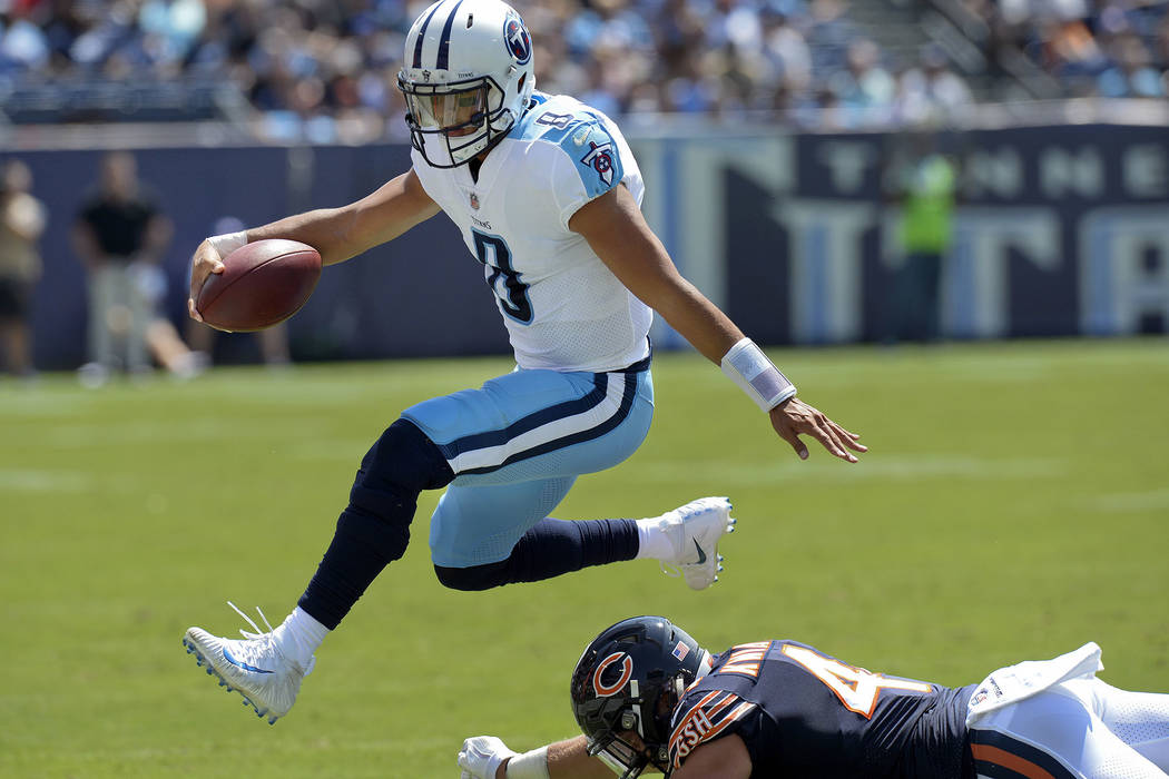 In this Aug. 27, 2017, file photo, Tennessee Titans quarterback Marcus Mariota (8) leaps over Chicago Bears inside linebacker Nick Kwiatkoski (44) in the first half of an NFL football preseason ga ...
