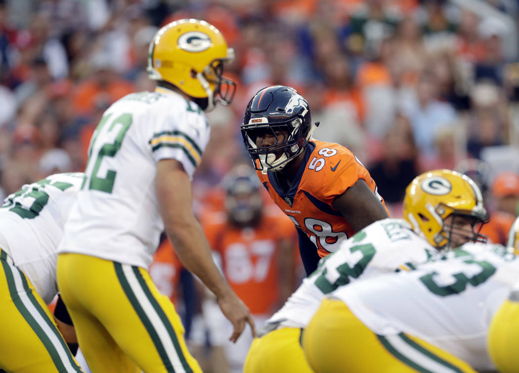 Denver Broncos outside linebacker Von Miller (58) eyes Green Bay Packers quarterback Aaron Rodgers (12) during the first half of an NFL preseason football game, Saturday, Aug. 26, 2017, in Denver. ...