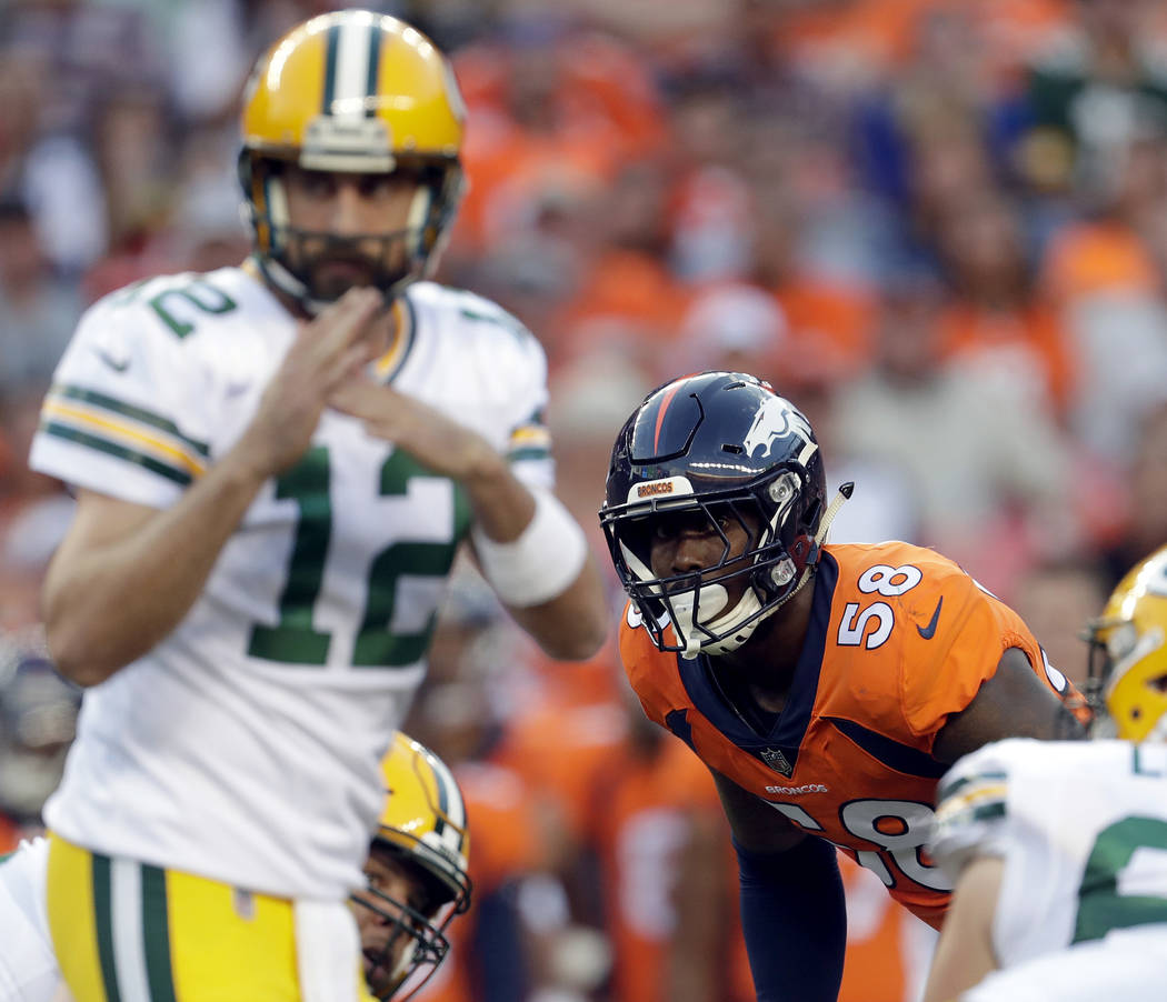 FILE - In this Aug. 26, 2017, file photo, Denver Broncos outside linebacker Von Miller (58) watches as Green Bay Packers quarterback Aaron Rodgers (12) calls time out during the first half of an N ...