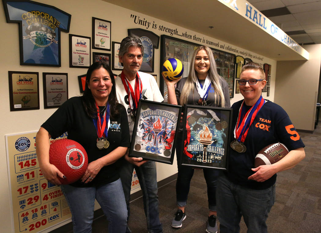 Cox employees and members of the Cox corporate challenge team, Cathy Hurley, left, Juergen Barbusca, Nadia Basich and Jillian Stradley, right, pose for photo with their awards on Wednesday, Jan. 3 ...