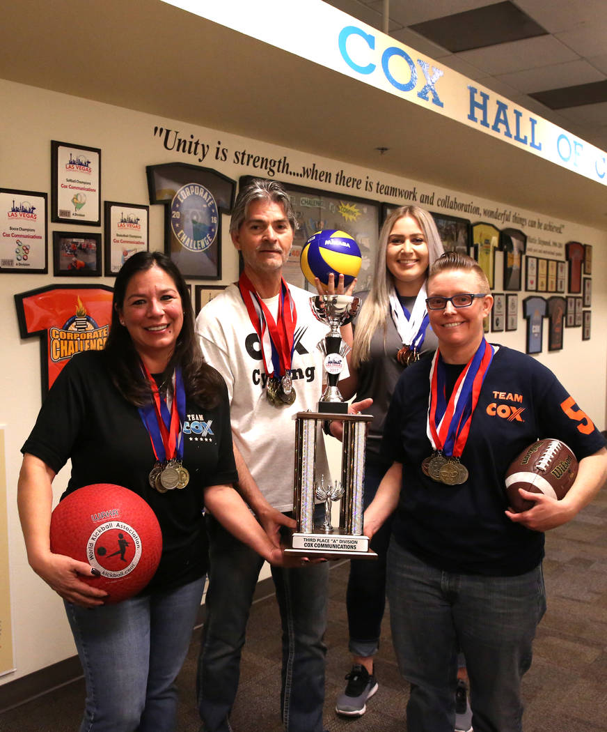 Cox employees and members of the Cox corporate challenge team, Cathy Hurley, left, Juergen Barbusca, Nadia Basich and Jillian Stradley, right, pose for photo with their medals and trophy on Wednes ...