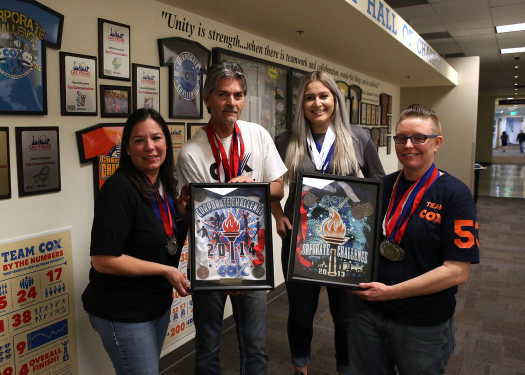 Cox Communications employees and members of the Cox corporate challenge team, Cathy Hurley, left, Juergen Barbusca, Nadia Basich and Jillian Stradley, right, pose for photo with their awards on We ...