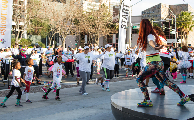 Participants await the start of the race and warm up by participating in a Zumba session prior to the start of the the 5k Color Run course near Fremont street area in downtown Las Vegas, Nev., Sat ...