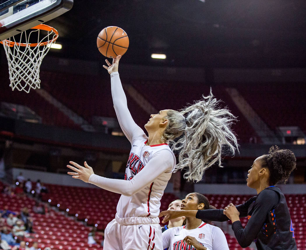 UNLV's Katie Powell (21) goes up for a shot while Jordyn Bell (23) and Boise State's A'Shanti Coleman (42), right, watch from below at the Thomas & Mack Center in Las Vegas on Saturday, Feb. 3 ...