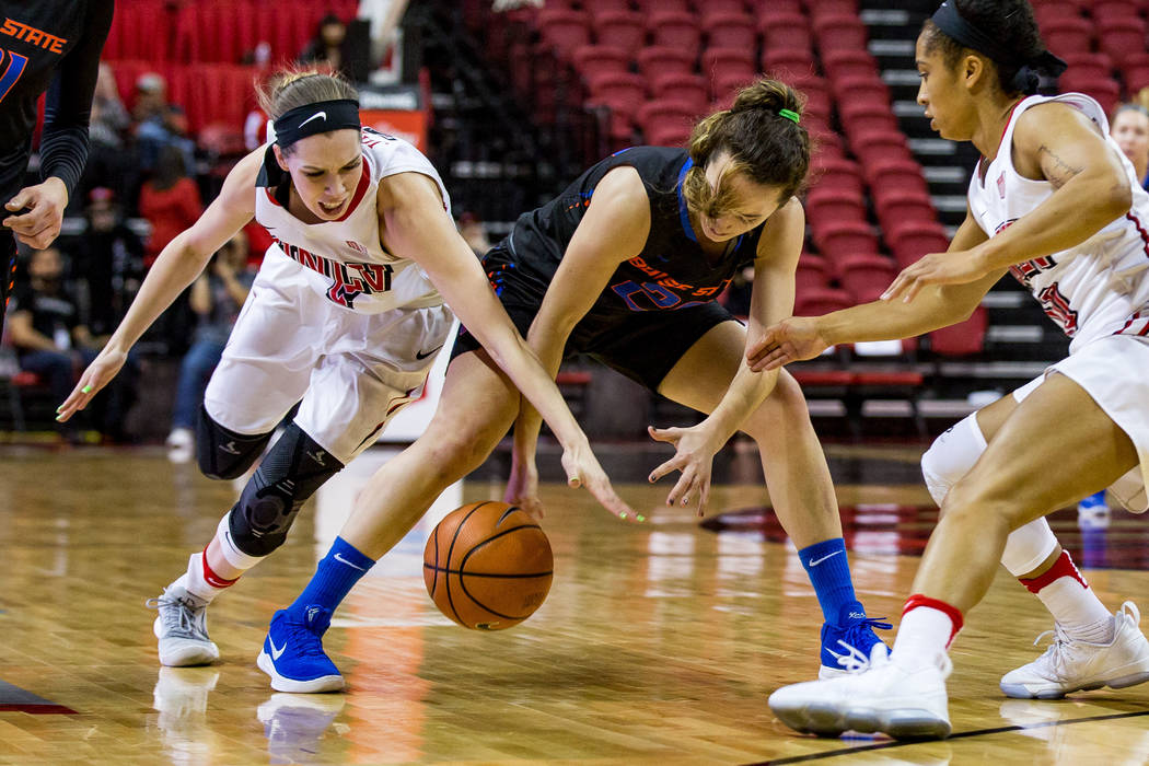UNLV's Brooke Johnson (2) and Boise State's Marta Hermida (20) grapple over the ball while UNLV's Nikki Wheatley (10) steps in to help at the Thomas & Mack Center in Las Vegas on Saturday, Feb ...