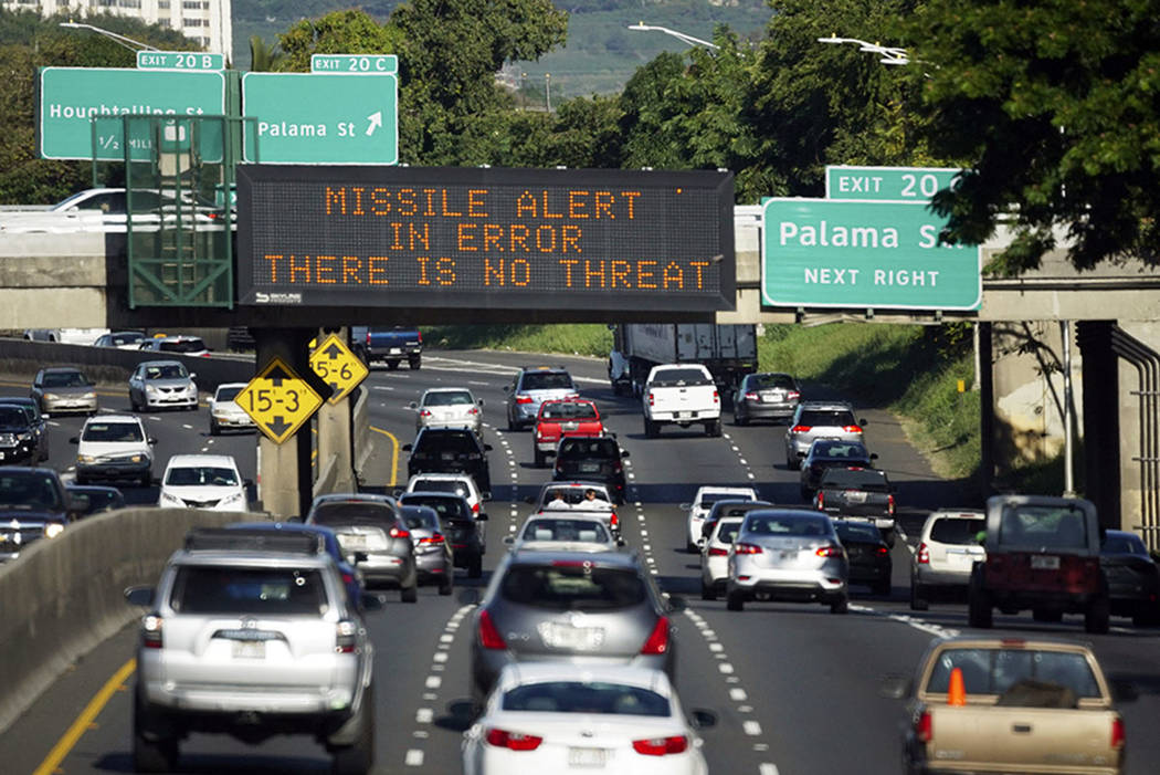 "Cars drive past a highway sign that says ""MISSILE ALERT ERROR THERE IS NO THREAT"" on the H-1 Freeway in Honolulu. (Cory Lum/Civil Beat via AP, File)"