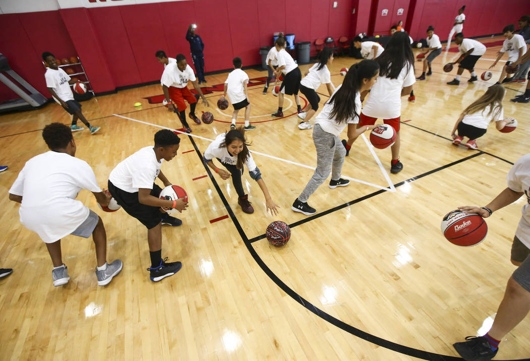 After-School All-Stars students from local middle schools dribble a basketball while participating in sports clinics led by UNLV student-athletes at Mendenhall Center at UNLV in Las Vegas on Satur ...