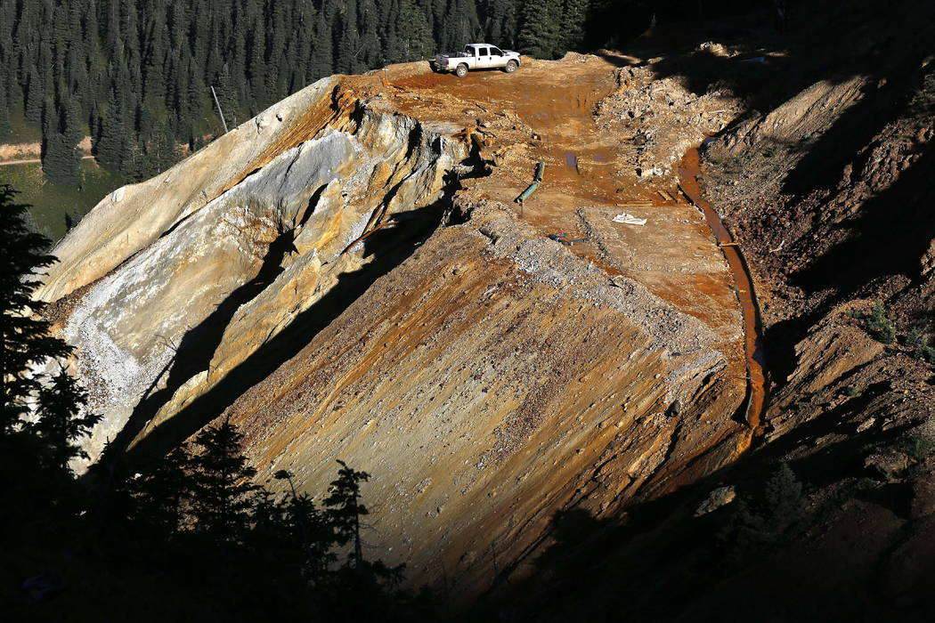 Wastewater flows down a trough, right, from the site of the blowout at the Gold King mine which triggered a major spill of toxic wastewater, outside Silverton, Colo., in 2015. (AP Photo/Brennan Li ...