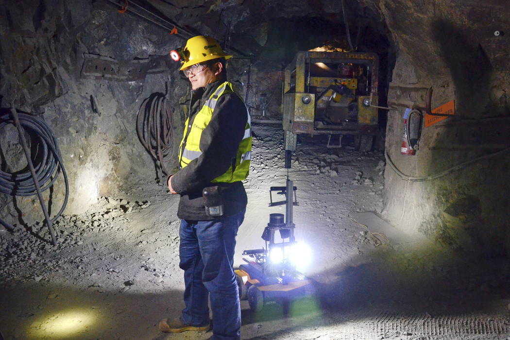 A miner is backed by a robot in the Edgar Mine near Denver in 2017. (AP Photo/Tatiana Flowers)
