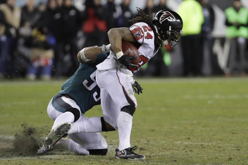 Atlanta Falcons' Devonta Freeman runs the ball as Philadelphia Eagles' Mychal Kendricks tries to bring him down during the second half of an NFL divisional playoff football game, Saturday, Jan. 13 ...