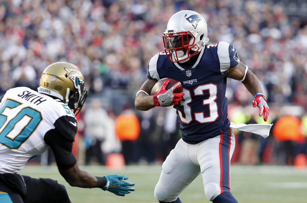 New England Patriots' Dion Lewis runs against Jacksonville Jaguars' Telvin Smith during the AFC Championship NFL football game at Gillette Stadium in Foxborough, Mass. Sunday, Jan. 21, 2018. (AP P ...