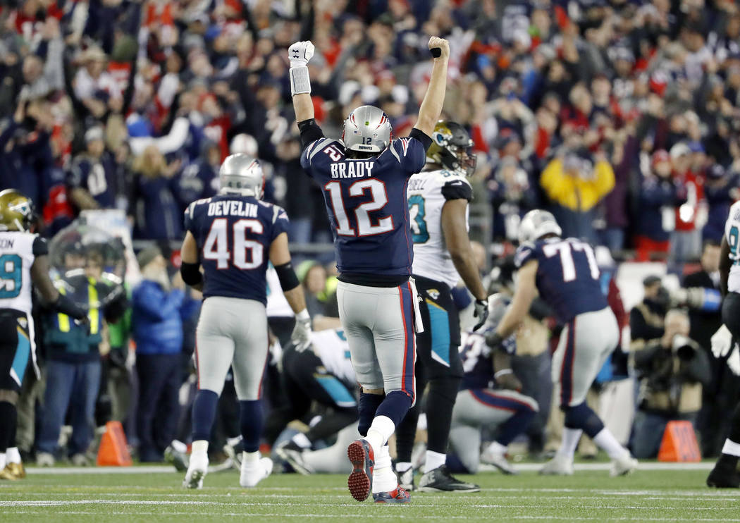 New England Patriots quarterback Tom Brady (12) celebrates a catch by wide receiver Phillip Dorsett during the second half of the AFC championship NFL football game against the Jacksonville Jaguar ...