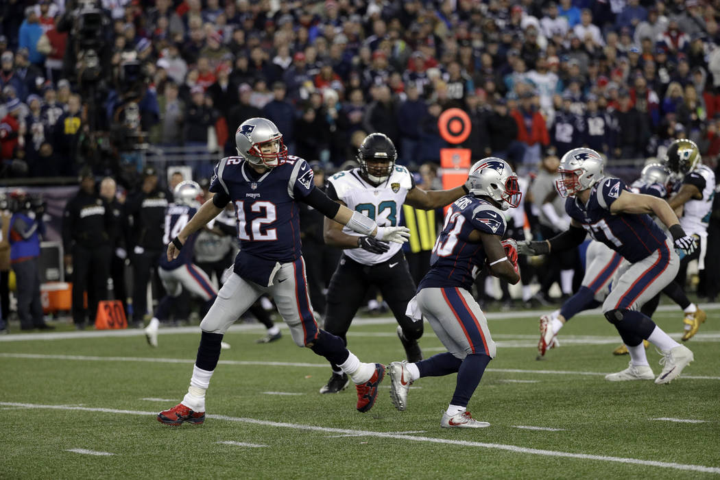 New England Patriots quarterback Tom Brady (12) hands off the ball to running back Dion Lewis (33) during the second half of the AFC championship NFL football game against the Jacksonville Jaguars ...