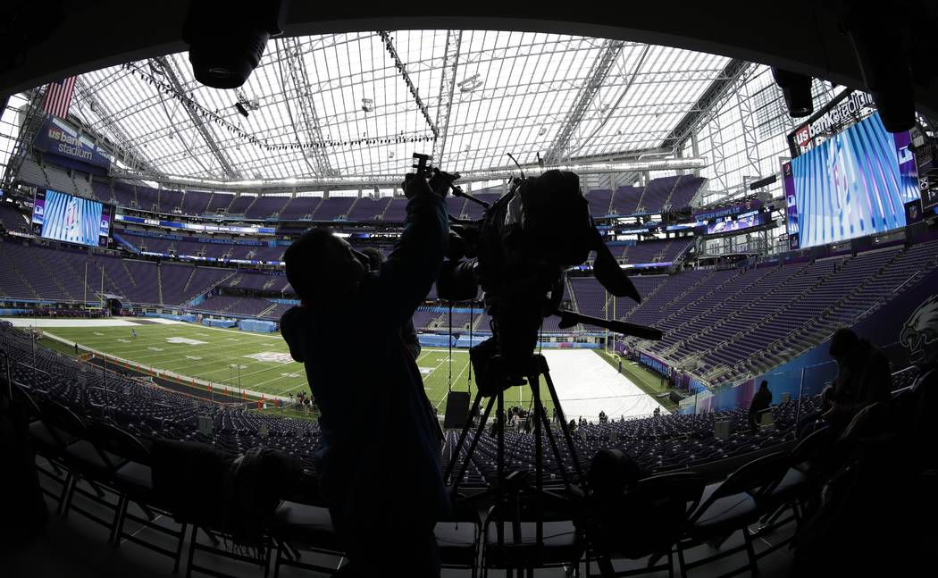 A videographer shoots video of U.S. Bank Stadium as workers get it ready for Super Bowl 52 on Tuesday, Jan. 30, 2018, in Minneapolis. (AP Photo/Matt Slocum)