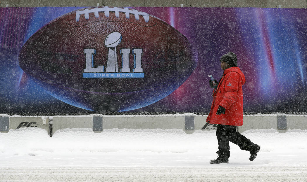 Snow falls as a woman passes signage for the NFL Super Bowl 52 football game at U.S. Bank Stadium, Saturday, Feb. 3, 2018, in Minneapolis. The Philadelphia Eagles are scheduled to face the New Eng ...