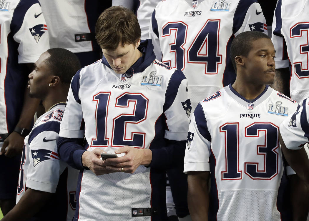 New England Patriots quarterback Tom Brady (12) checks his phone before the team photo is made in U.S. Bank Stadium Saturday, Feb. 3, 2018, in Minneapolis. The Patriots are scheduled to face the P ...