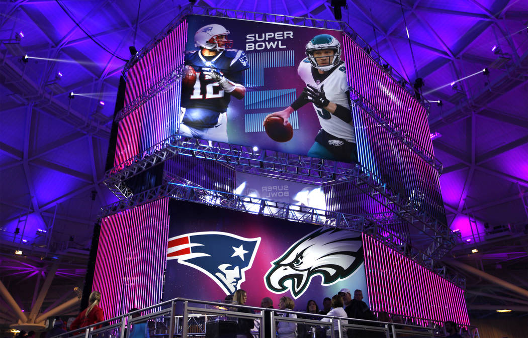 A banner featuring New England Patriots quarterback Tom Brady, left, and Philadelphia Eagles quarterback Nick Foles is a centerpiece inside the NFL Experience at the Minneapolis Convention Center  ...