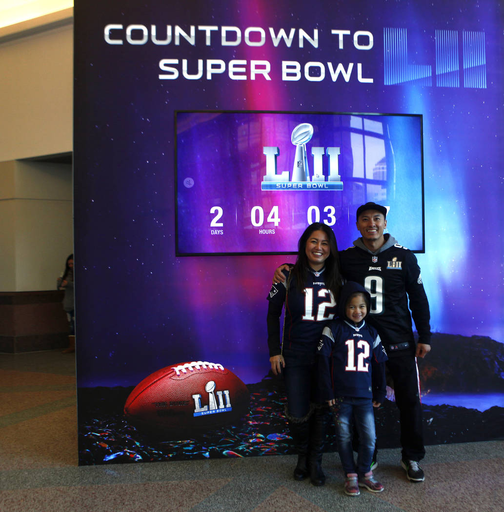 Shoua Chang, left, and Perseyeus Chang, middle, don Tom Brady New England Patriots jerseys, while Early Chang wears a Nick Foles Philadelphia Eagles jersey at the NFL Experience at the Minneapolis ...