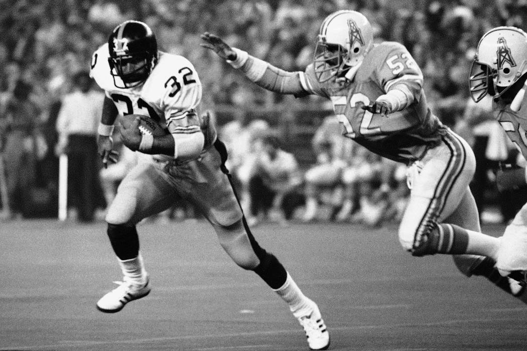 Pittsburgh Steelers running back Franco Harris (32) picks up 10 yards as he turns the corner as Houston Oilers' Robert Brazile (52) makes a dive to latch on to Harris to make the stop, during an N ...