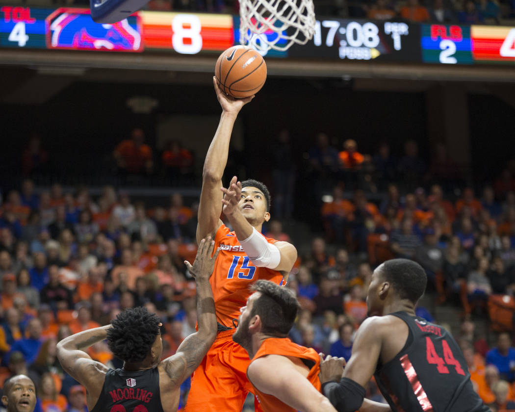 Boise State's Chandler Hutchison (15) shoots over UNLV's Jovan Mooring, left, during the first half of an NCAA college basketball game in Boise, Idaho, Saturday, Feb. 3, 2018. (AP Photo/Otto Kitsi ...