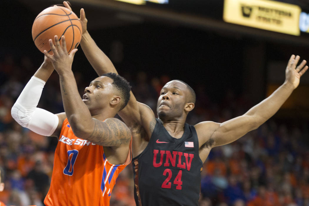 Boise State's Marcus Dickinson (0) shoots past UNLV's Jordan Johnson (24) during the first half of an NCAA college basketball game in Boise, Idaho, Saturday, Feb. 3, 2018. (AP Photo/Otto Kitsinger)