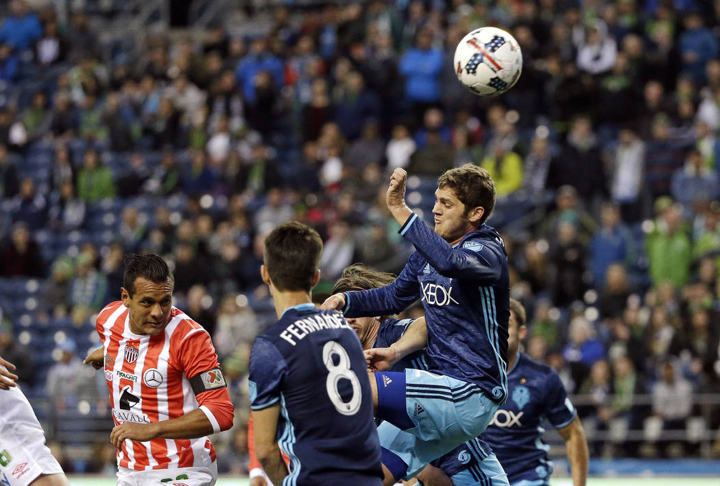 Zach Mathers, right, leaps toward the ball during the first half of a soccer match in this 2017 file photo when he was with the Seattle Sounders. (AP Photo/Elaine Thompson)