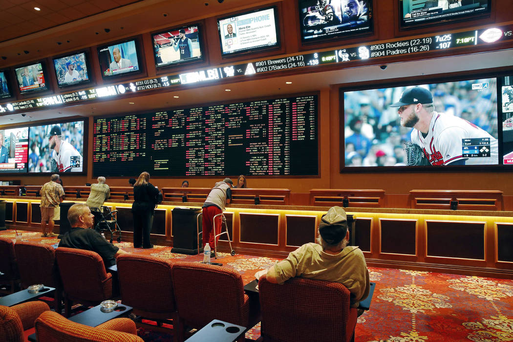 People make bets in the sports book at the South Point hotel and casino in Las Vegas in May 2018. (AP Photo/John Locher)