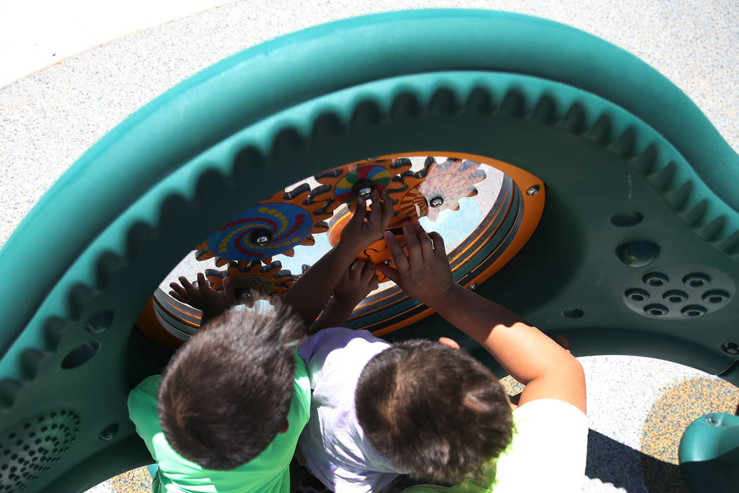 Children play with the newly installed sensory wall at Gilcrease Brothers Park in Las Vegas, Saturday, June 23, 2018. The sensory wall is the first to be installed in a city park according to Fior ...