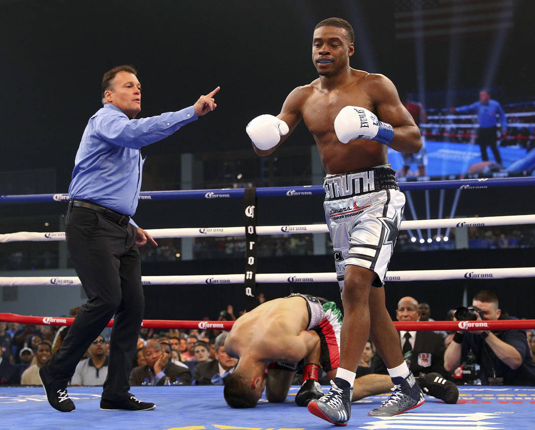 Referee Laurence Cole sends Errol Spence Jr. to a neutral corner after Carlos Camp went down during the first round of a welterweight boxing match Saturday, June 16, 2018, in Frisco, Texas. (AP Ph ...