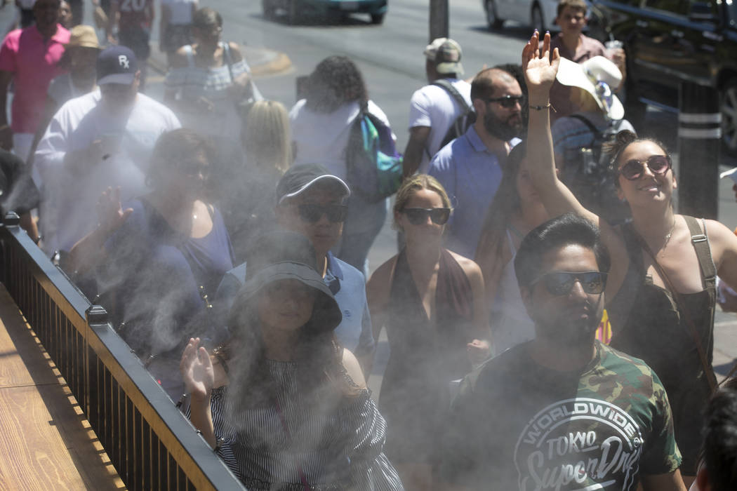 People cool off under a water mister outside the Hexx Kitchen and Bar on the Las Vegas Strip on Thursday, June 21, 2018. (Richard Brian/Las Vegas Review-Journal) @vegasphotograph